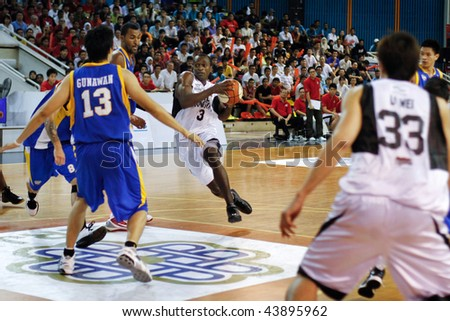 KUALA LUMPUR - JANUARY 05: KL Dragons' Chris Kuete charges at the Satria Muda BritAma at the ASEAN Basketball League match January 05, 2010 in Kuala Lumpur. - stock photo