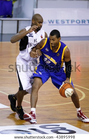 KUALA LUMPUR - JANUARY 05: KL Dragons' Jamal Brown defends Satria Muda BritAma's Nakiea Miller at the ASEAN Basketball League match January 05, 2010 in Kuala Lumpur. - stock photo