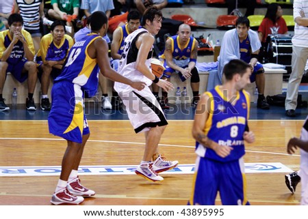 KUALA LUMPUR - JANUARY 05: KL Dragons' Li Wei attempts to get past Satria Muda BritAma's Nakiea Miller (43) at the ASEAN Basketball League match January 05, 2010 in Kuala Lumpur. - stock photo