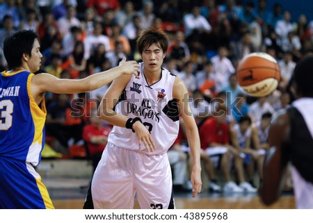 KUALA LUMPUR - JANUARY 05: KL Dragons' Li Wei making a pass against Satria Muda BritAma at the ASEAN Basketball League match January 05, 2010 in Kuala Lumpur. - stock photo