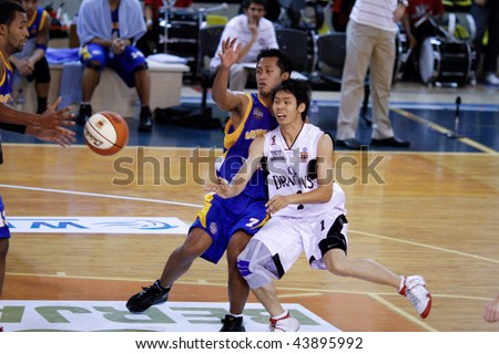 KUALA LUMPUR - JANUARY 05: KL Dragons' Wee Chin Chuan (#1) hustles with  Satria Muda BritAma's Prihantono (#7) at the ASEAN Basketball League match. January 05, 2010 in Kuala Lumpur. - stock photo