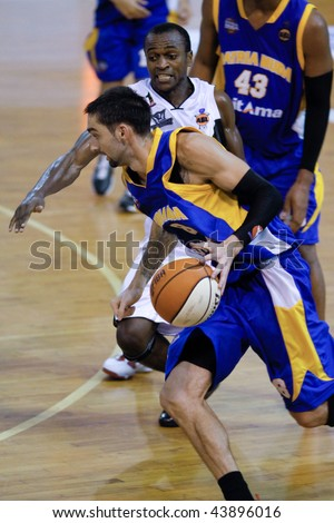 KUALA LUMPUR - JANUARY 05: Satria Muda BritAma's Alex Hartman (8) dribbles past KL Dragons' Chris Kuete at the ASEAN Basketball League match January 05, 2010 in Kuala Lumpur. - stock photo