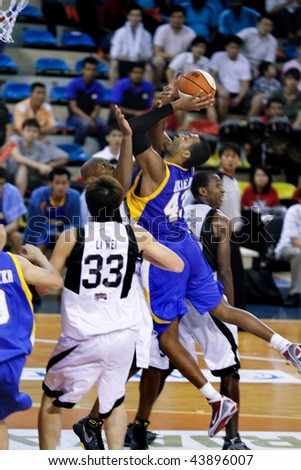 KUALA LUMPUR - JANUARY 05: Satria Muda BritAma's Nakiea Miller attempts a shot defended by Jamal Brown and Li Wei (33) at the ASEAN Basketball League match January 05, 2010 in Kuala Lumpur. - stock photo