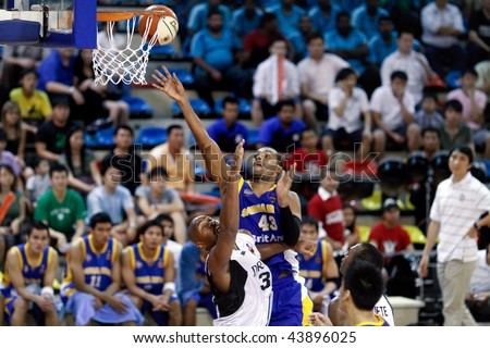 KUALA LUMPUR - JANUARY 05: Satria Muda BritAma's Nakiea Miller (43) outjumps KL Dragons' Jamal Brown to tip in a rebound at the ASEAN Basketball League match January 05, 2010 in Kuala Lumpur. - stock photo