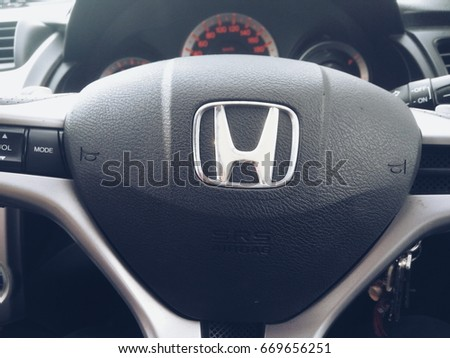 KUALA LUMPUR, January 13, 2016 : View of a hand holding HONDA steering and meter. Focus on HONDA logo. A crop close up steering wheels