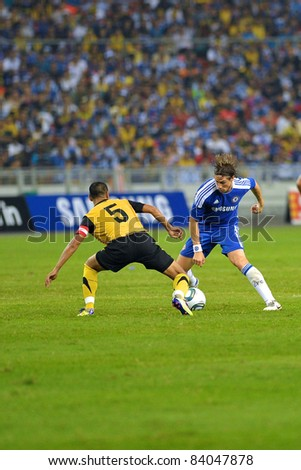 KUALA LUMPUR, July 21: Chelsea's Fernando Torres (blue) and Malaysian Nurhafiz Zamani (5) in action during a preseason match agains Malaysia on July 21, 2011 in Kuala Lumpur, Malaysia. Chelsea won 1-0 - stock photo