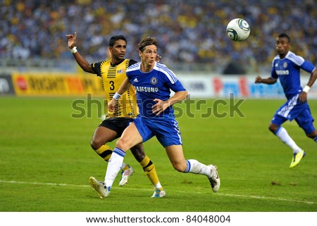 KUALA LUMPUR, July 21 : Chelsea's Fernando Torres (center blue) and Malaysian S.Subramaniam (3) in action during a preseason match agains Malaysia on July 21, 2011 in Kuala Lumpur, Malaysia. - stock photo