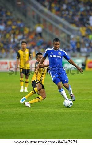 KUALA LUMPUR, July 21 : Chelsea's Florent Malouda (blue) and Malaysian Badri Radzi (8) in action during a preseason match agains Malaysia on July 21, 2011 in Kuala Lumpur, Malaysia. Chelsea won 1-0 - stock photo