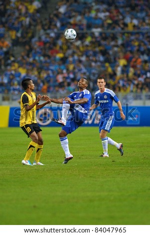 KUALA LUMPUR, July 21 : Chelsea's Florent Malouda (center in blue) and Malaysian Badri Radzi (8) in action during a preseason match agains Malaysia on July 21, 2011 in Kuala Lumpur, Malaysia - stock photo