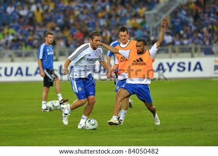 KUALA LUMPUR, JULY 21 : Chelsea's Frank Lampard (in white) Josh McEachran (center) Jose Bosingwa (R)  warm-up during a preseason match against Malaysia on July 21, 2011 in Kuala Lumpur, Malaysia. - stock photo