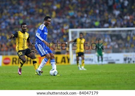 KUALA LUMPUR, July 21 : Chelsea's John Obi Mikel (blue) and Malaysian Gary Stevan (12) in action during a preseason match agains Malaysia on July 21, 2011 in Kuala Lumpur, Malaysia. Chelsea won 1-0 - stock photo