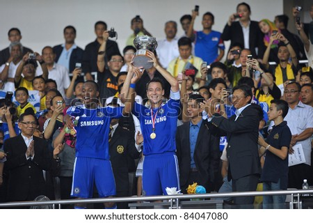 KUALA LUMPUR, July 21 : Chelsea's John Terry (right) and Didier Drogba (Left) happy on stage during a preseason match agains Malaysia on July 21, 2011 in Kuala Lumpur, Malaysia. Chelsea won 1-0 - stock photo