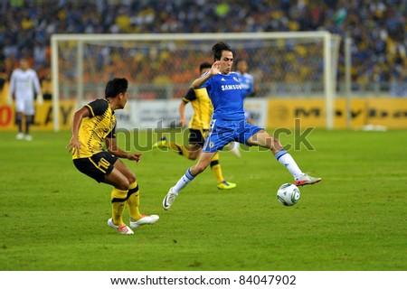 KUALA LUMPUR, July 21 : Chelsea's Yossi Benayoun (blue) and Malaysian Fandi Othman (10) in action during a preseason match agains Malaysia on July 21, 2011 in Kuala Lumpur, Malaysia. Chelsea won 1-0 - stock photo