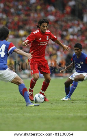 KUALA LUMPUR - JULY 16 : Liverpool football club player Alberto Aquilani (C) controls a ball during a friendly match against Malaysia XI on July 16, 2011 in Kuala Lumpur, Malaysia. Liverpool won 6-3. - stock photo