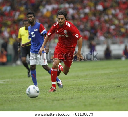 KUALA LUMPUR - JULY 16 : Liverpool football club player Alberto Aquilani (R) controls a ball during a friendly match against Malaysia XI on July 16, 2011 in Kuala Lumpur, Malaysia. Liverpool won 6-3. - stock photo