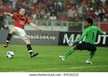 KUALA LUMPUR- JULY 20: Wayne Rooney (L) of Manchester United and Malaysia Goal Keeper Farizal Marlias in action during friendly match (2nd Match) against Malaysia, July 20, 2009 in Kuala Lumpur. - stock photo