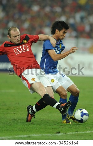 KUALA LUMPUR- JULY 20: Wayne Rooney (L) of Manchester United and Malaysian, Muslim Ahmad (R) in action during friendly match (2nd Match) against Malaysia, July 20, 2009 in Kuala Lumpur. - stock photo
