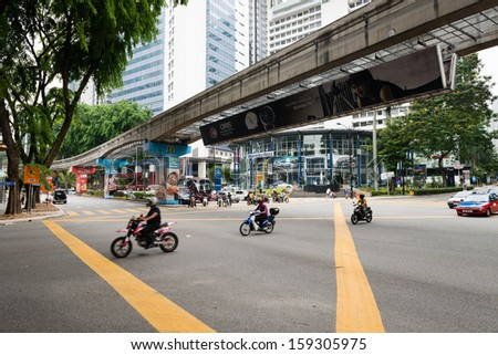 KUALA LUMPUR - JUN 15: City street with motorbikes and  monorail way under road on Jun 15, 2013 in Kuala Lumpur, Malaysia. Three separate rail systems with underground, elevated or at-grade lines. - stock photo