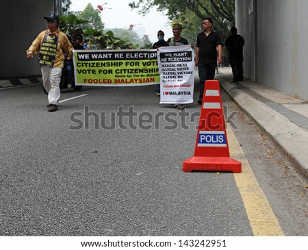 KUALA LUMPUR - JUNE 22: Protesters march with political banner at the protest rally against election fraud on June 22, 2013 in Jalan Parlimen, Kuala Lumpur, Malaysia.