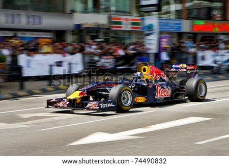 KUALA LUMPUR, MALAYSIA - APR 3 : Former Red Bull F1 driver David Coulthard of Britain steers his car during a street demonstration on April 3, 2011 in downtown Kuala Lumpur, Malaysia. - stock photo