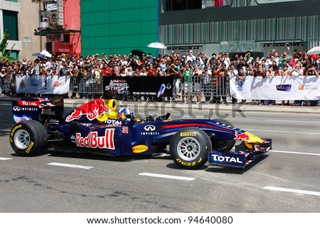 KUALA LUMPUR, MALAYSIA-APR 3:Former Red Bull F1 driver David Coulthard steers his car during a street demonstration Apr 3, 2011 in Kuala Lumpur.The event is a promotion for F1 Malaysia Grand Prix 2011 - stock photo
