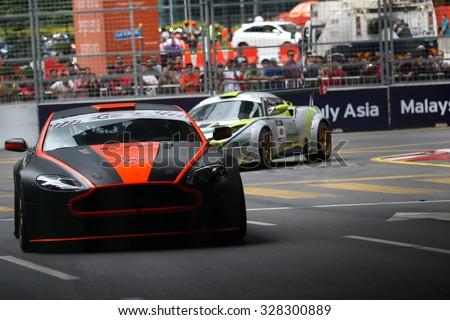 KUALA LUMPUR, MALAYSIA - AUGUST 08, 2015: Gerard Yap drives a Vantage N24 GT4 car (orange/black) takes turn 2 at the inaugural 2015 Kuala Lumpur City Grand Prix. - stock photo