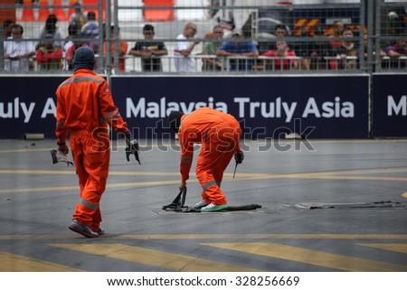 KUALA LUMPUR, MALAYSIA - AUGUST 08, 2015: Street race marshals clean the race track before the Lamborghini Blancpain Super Trofeo Race, at the 2015 Kuala Lumpur City Grand Prix. - stock photo