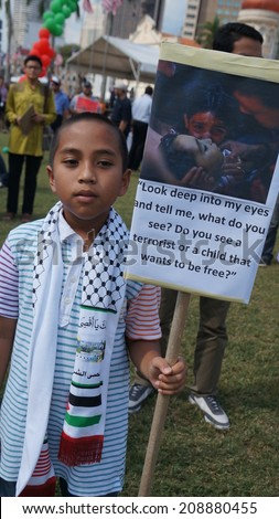 Kuala Lumpur, Malaysia - August, 2: Unidentified Malaysian children holds sign protesting Israeli military strikes on Gaza, during the pro-Palestine rally in Kuala Lumpur, August 2, 2014. - stock photo