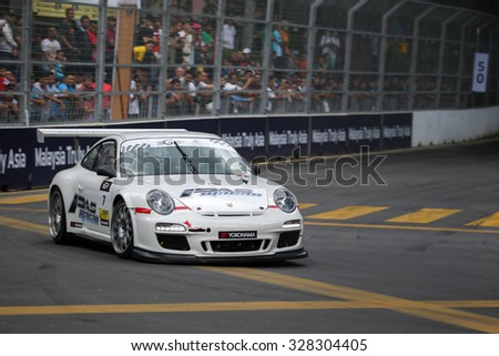 KUALA LUMPUR, MALAYSIA - AUGUST 08, 2015: Wong Kiang Kuan drives a Porsche 997 car takes turn 2 of the city streets in the KL City GT CUP Race of the 2015 Kuala Lumpur City Grand Prix. - stock photo