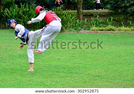 Kuala Lumpur, Malaysia - December 29, 2013. Martial arts fighters in action. Two sparing partners in action during taekwondo training. Taekwondo is one of the famous martial art in Malaysia. - stock photo