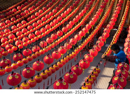 KUALA LUMPUR, MALAYSIA - FEBRUARY 08, 2015: An unidentified worker hangs red lanterns across the courtyard of the Thean Hou Temple in preparation for the coming Chinese New Year celebrations. - stock photo