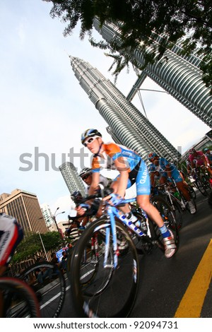 KUALA LUMPUR, MALAYSIA-FEBRUARY 15: Cyclists pedal their way in front of the iconic KLCC building landmark during the Le Tour de Langkawi competition in Kuala Lumpur,Malaysia on February 15,2009. - stock photo