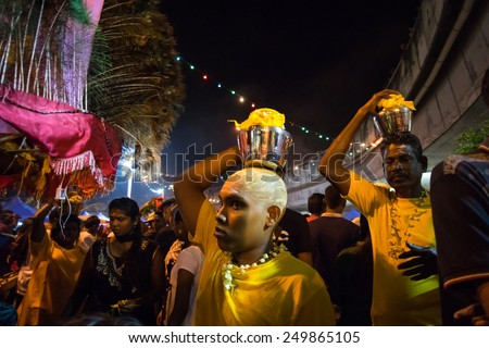 KUALA LUMPUR, MALAYSIA - FEBRUARY 3, 2015: Hindu devotees carry milk pots and kavadis walk in a procession to the Batu Caves temple on Thaipusam day, a day of thanksgiving and devotion. - stock photo