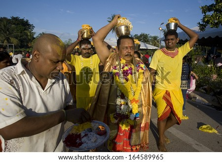 Kuala Lumpur, Malaysia, January 27 2013: A Hindu devotee carry a pot of milk each during Thaipusam festival to fulfill their vows and offer thanks to the deities. - stock photo