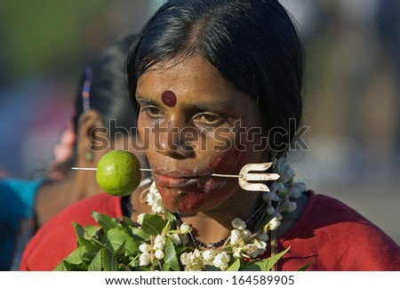 Kuala Lumpur, Malaysia, January 27 2013: A Hindu devotee with skewer protruding through her cheek during Thaipusam festival to fulfill their vows and offer thanks to the deities. - stock photo