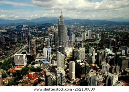 Kuala Lumpur, Malaysia - January 2, 2008: Panoramic view of the city with the soaring 1,482 foot high twin Petronas Towers at the center - stock photo