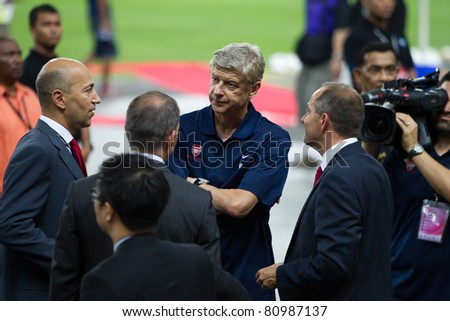 KUALA LUMPUR, MALAYSIA - JULY 13: Arsenal manager, Arsene Wenger, center, in the blue T-shirt, chats before the start of Arsenal vs.  Malaysia friendly football match on July 13, 2011 in  Kuala Lumpur, Malaysia