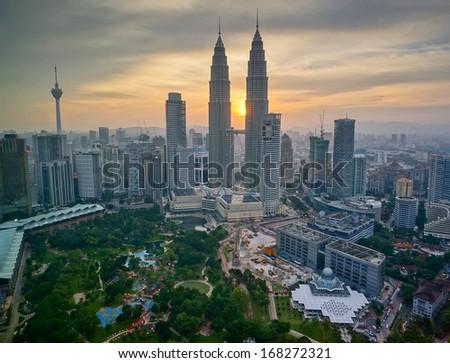 KUALA LUMPUR, MALAYSIA - JULY 20: Petronas Twin Towers at sunset on July 20, 2013 in Kuala Lumpur. Currently the Petronas are the tallest twin towers in the world.  - stock photo