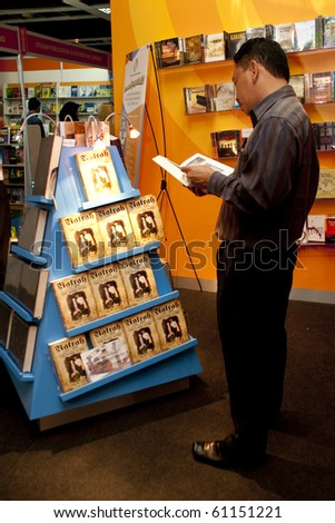 KUALA LUMPUR, MALAYSIA - MARCH 24 : A Visitor to KLIBF read a book on Natrah or Maria Hertogh - Malaysia's & Singapore's Most Famous Child Custody Victim March 24, 2010 in Kuala Lumpur Malaysia. - stock photo