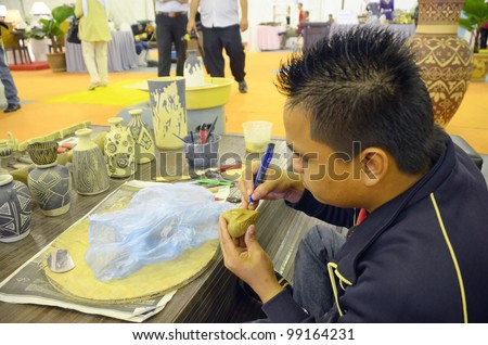 KUALA LUMPUR, MALAYSIA - MARCH 30: An artist show carved vase by exhibitors during the exhibition of the National Craft Day 2012 at the Kuala Lumpur Craft Complex on March 30, 2012 in Kuala Lumpur - stock photo