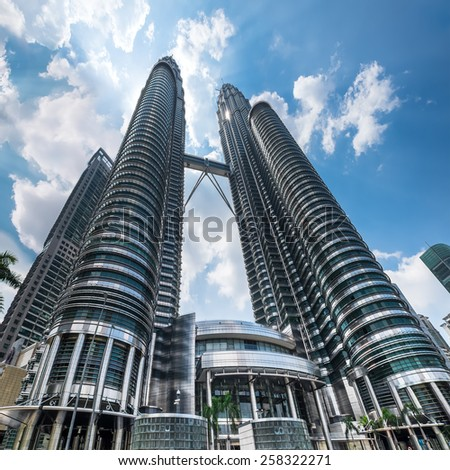 KUALA LUMPUR, MALAYSIA - March 4, 2015: Cloudscape view of the Petronas Twin Towers at KLCC City Center. The most popular tourist destination in Malaysian capital - stock photo