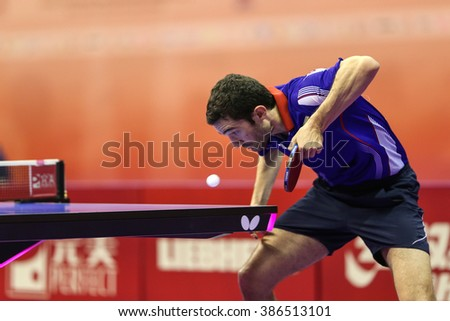 KUALA LUMPUR, MALAYSIA - MARCH 01, 2016: Emmanuel Lebesson of France plays a return shot in his match in the Perfect 2016 World Team Table-tennis Championships held in Kuala Lumpur, Malaysia. - stock photo