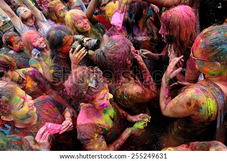 KUALA LUMPUR, MALAYSIA - MARCH 18: Photographer and people covered in paint on Holi festival, March 18, 2013, Malaysia. Holi festival of colors, being one of the biggest festivals in Malaysia. - stock photo