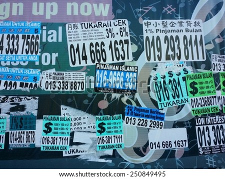 KUALA LUMPUR, MALAYSIA-MAY 26, 2014: Post-it notes from illegal money lender offering easy money borrowing in Kuala Lumpur, Malaysia. These money lender normally offer high interest rate. - stock photo
