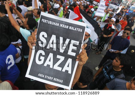 "KUALA LUMPUR, MALAYSIA-NOV 16: A man holds a poster ""SAVE GAZA"" infront of US Embassy in Kuala Lumpur, Malaysia on November 16. 2012. Israeli assault on Gaza has spread outrage over muslims country."