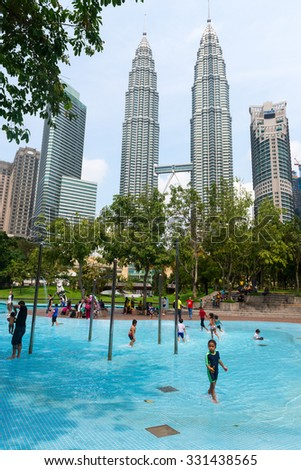 KUALA LUMPUR, MALAYSIA - 02 NOV 2014: Children swimming pool in KL City park with Petronas Twin Towers on background. Having fun in clear blue water - stock photo