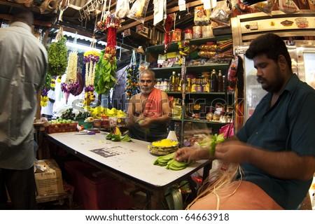 KUALA LUMPUR, MALAYSIA - NOVEMBER 5:  Temple workers prepare prayer items for sale at the temple stall on Diwali celebrations day, November 5, 2010 at the Hanuman Temple, Kuala Lumpur. - stock photo