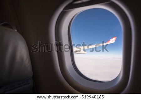 Kuala Lumpur, Malaysia - Oct 29, 2016: Window view of wing of an AirAsiaX aeroplane  with blue sky. Recently, they was awarded as the Worldâ??s Best Low-Cost Airline for the 8th consecutive year.