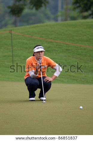 KUALA LUMPUR, MALAYSIA - OCTOBER 16: Amy Yang of South Korea lines up for her putt at the Sime Darby LPGA Malaysia 2011 in Kuala Lumpur Golf & Country Club, Malaysia on October 16, 2011. - stock photo