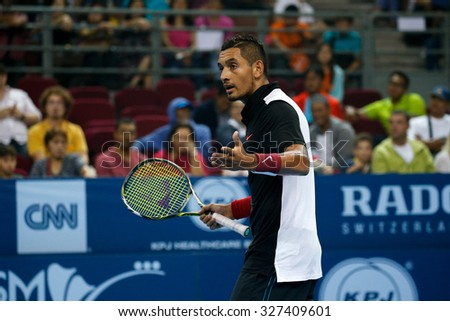 KUALA LUMPUR, MALAYSIA - OCTOBER 03, 2015: Australia's tennis player Nick Kyrgios checks with the chair umpire over a call at the 2015 Malaysian Open tennis tournament in Stadium Putra. - stock photo
